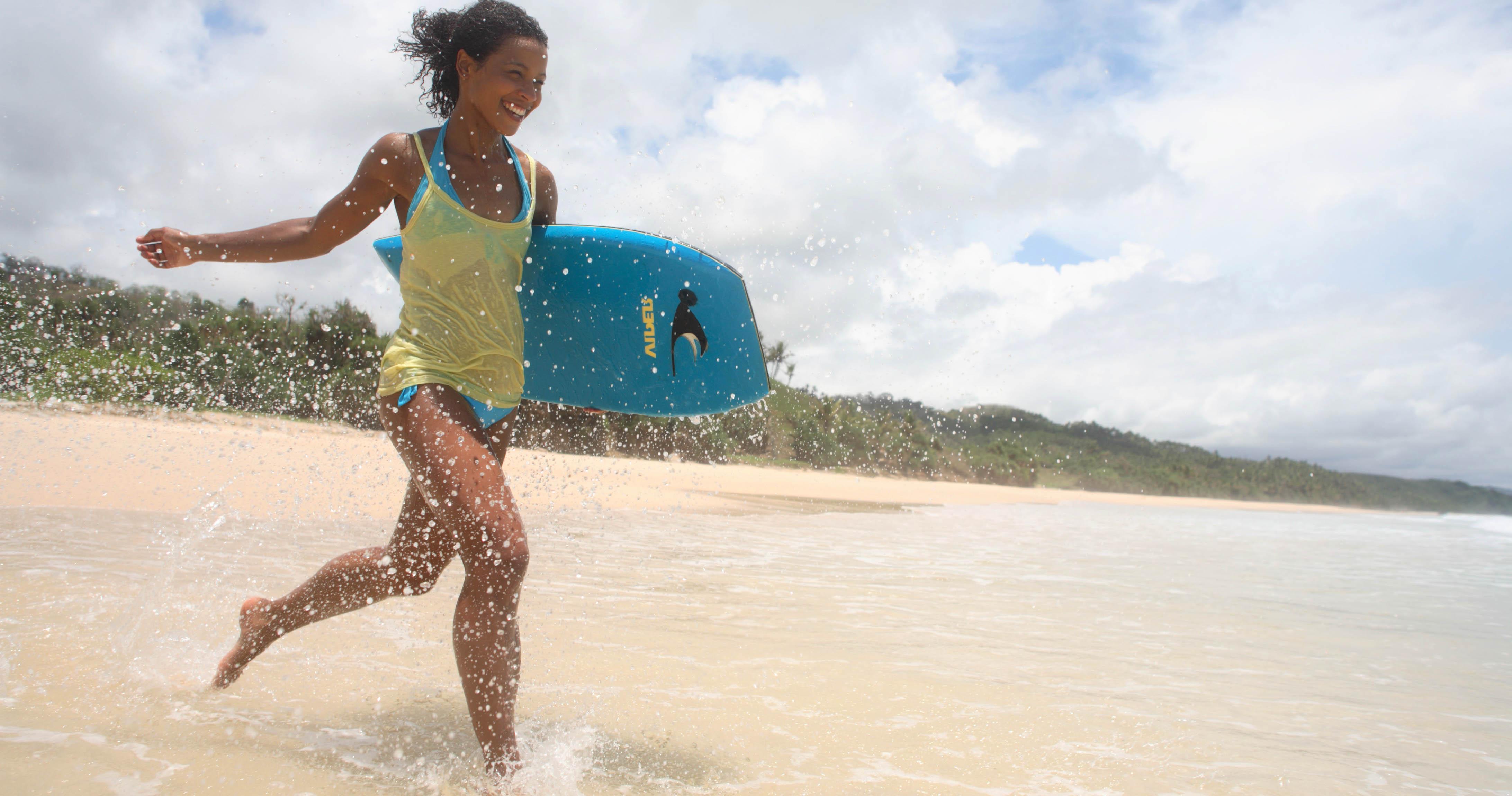 British female Voiceover Artist running down the beach