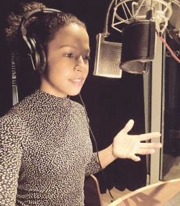 download and listen to voiceover demos. Bame female voice artist at microphone with home studio